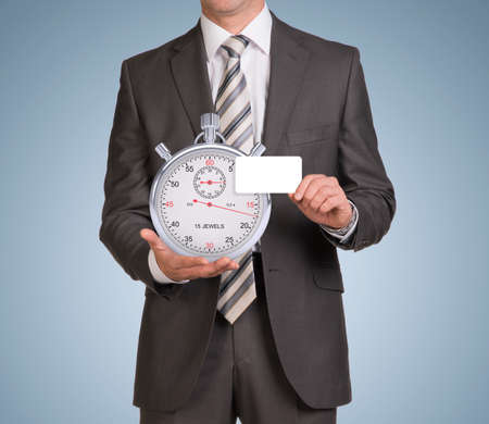 Businessman in suit hold empty card and stopwatch photo