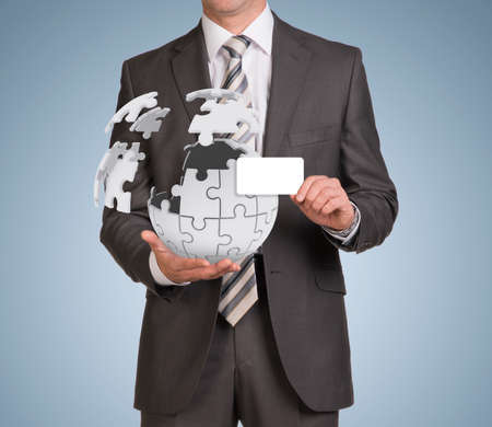 Man hold empty card and jigsaw puzzle sphere photo