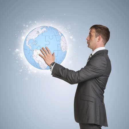 Businessman in suit hold earth globe consisting of puzzles photo