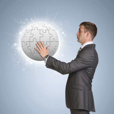 Businessman in suit hold jigsaw puzzle sphere photo