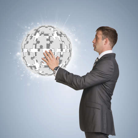 Businessman in suit hold and jigsaw puzzle sphere photo