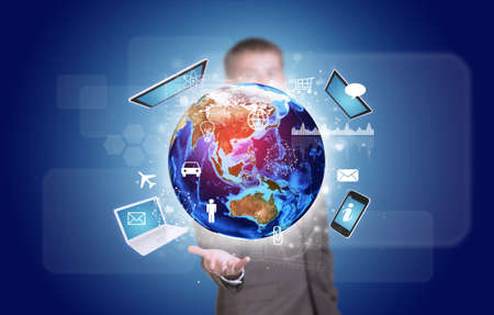 Businessman in suit hold Earth with electronics, graphs and icons photo