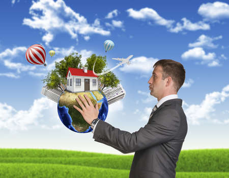 Businessman hold Earth with small house and trees photo