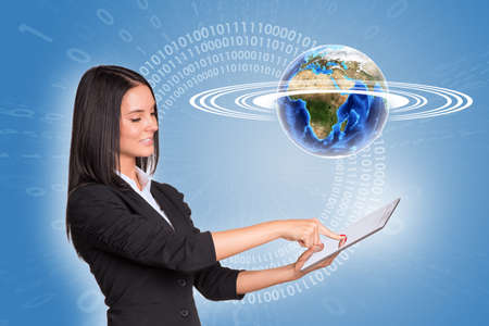 Beautiful businesswoman using tablet and Earth with figures photo