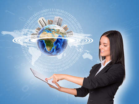 Woman using tablet. Earth with buildings and world map photo