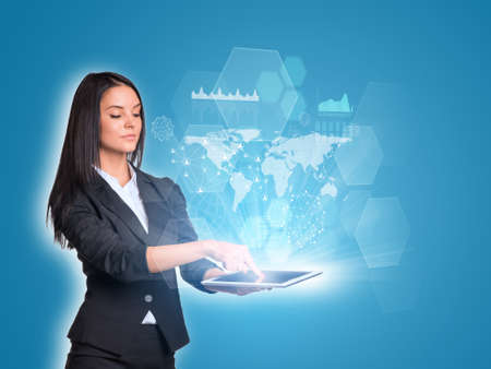Women using digital tablet and world map with transparent hexagons photo