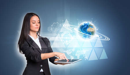 using tablet: Women using digital tablet and Earth triangles Stock Photo