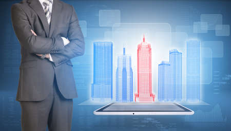 Businessman and wire-frame buildings on screen tablet pc photo