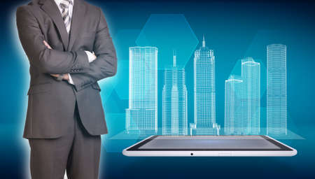 Businessman and wire-frame buildings on screen tablet photo