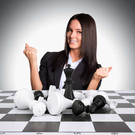 pawn adult: Joyful businesswoman wins chess and raised his hands up. Business concept Stock Photo