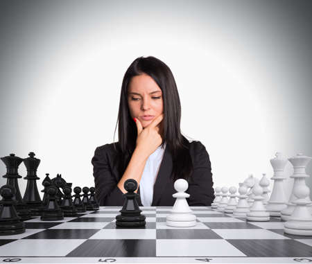 Lost in thought businesswoman looking at chess board with chess. Gray background. Business concept