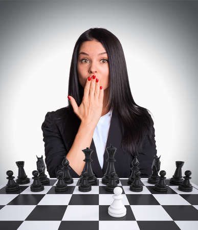 pawn adult: Surprised businesswoman looking at camera. Chessboard with chess. Gray background. Business concept