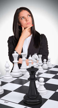 pawn adult: Lost in thought businesswoman up. Chessboard with chess. Gray background. Business concept