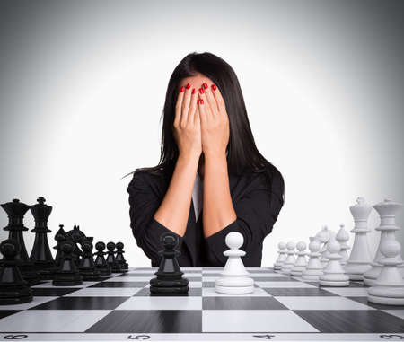 Businesswoman covering her face with hands. Chessboard with chess. Gray background. Business concept photo