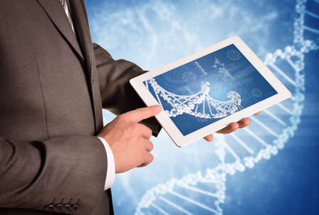 Man hands using tablet pc. Image of DNA helix on tablet screen photo
