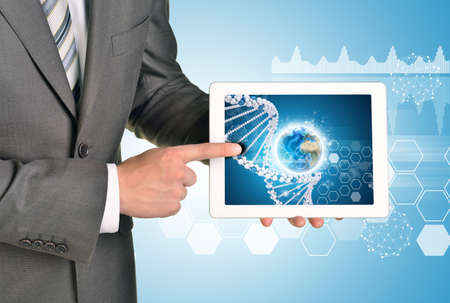Man hands using tablet pc. Image of Earth and DNA helix on tablet screen.  photo