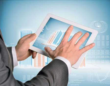 Man hands using tablet pc. Image of wire-frame buildings and open book on tablet screen photo
