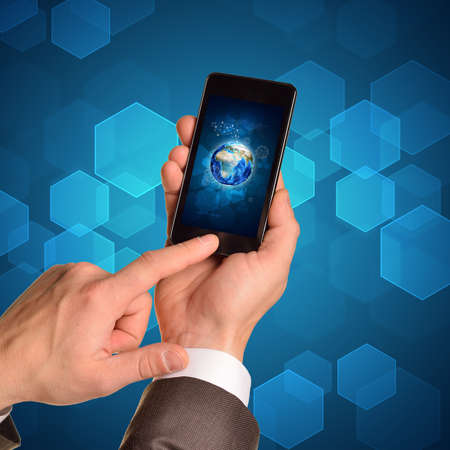 using smart phone: Man hands using smart phone. Image of Earth on phone screen.  Stock Photo