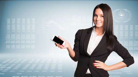 Businesswoman holding smart phone and smiling. High-tech graphs at backdrop photo