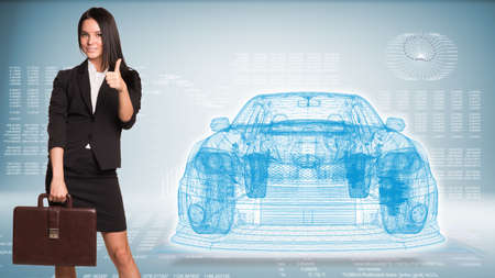 Businesswoman holding briefcase and showing thumb up. Wire-frame car and high-tech graphs as backdrop photo