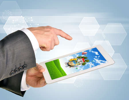 using tablet: Man hands using tablet pc. Image of Earth and house on tablet screen.