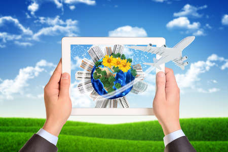 Man hands using tablet pc. Image of Earth and buildings on tablet screen.  photo