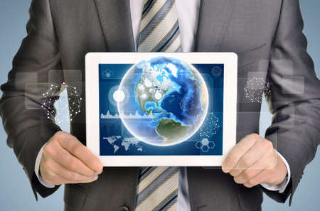using tablet: Man hands using tablet pc. Image of Earth and business elements on tablet screen.