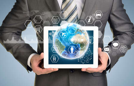 Man hands using tablet pc. Image of Earth and hexagons with icons on tablet screen.  photo