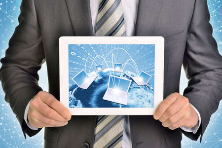 using tablet: Man hands using tablet pc. Image of Earth and laptops on tablet screen.  Stock Photo