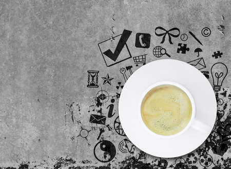 Coffee cup on concrete floor with various social icons. Business concept photo