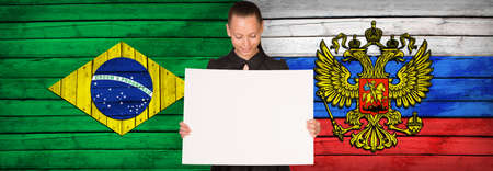foreign secretary: Businesswoman holding paper sheet. Brazil and Russia flags as backdrop Stock Photo