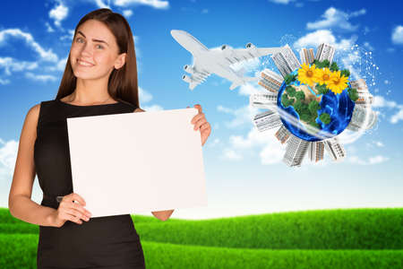Businesswoman holding empty paper. Earth with buildings and nature landscape as backdrop. photo