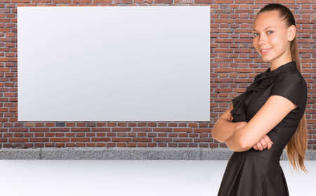 Businesswoman standing with crossed arms. Brickwall with empty billboard as backdrop photo