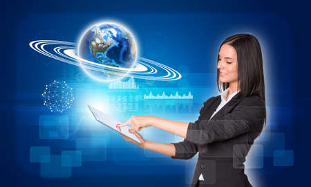 Beautiful businesswomen in suit using digital tablet. Earth with rectangles, graphs and wire-frame spheres.  photo