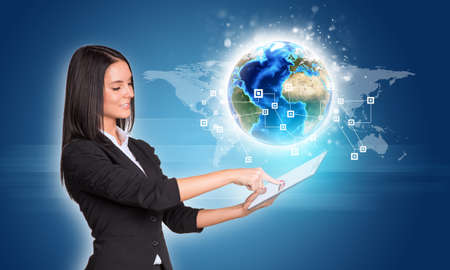 Beautiful businesswomen in suit using digital tablet. Earth with network and world map. photo