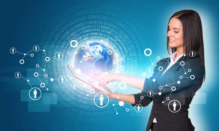Beautiful businesswomen in suit using digital tablet. Earth with figures and network. photo