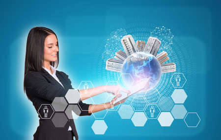 Beautiful businesswomen in suit using digital tablet. Earth with buildings. Hexagons and figures as backdrop.  photo