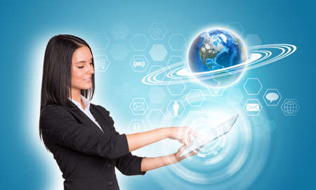 Beautiful businesswomen in suit using digital tablet. Earth and hexagons with icons.  photo