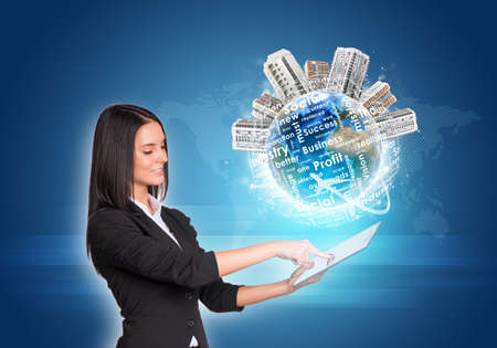 Beautiful businesswomen in suit using digital tablet. Earth with buildings and business words. World map as backdrop.  photo