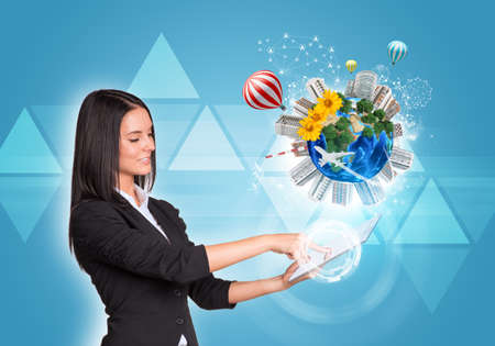 Beautiful businesswomen in suit using digital tablet. Earth with buildings, flowers, airplane and air balloons. Triangles as backdrop.  photo