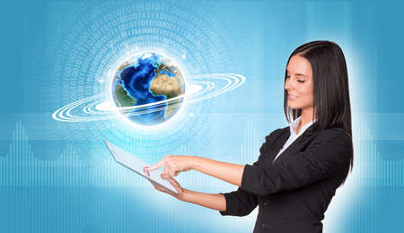Beautiful businesswomen in suit using digital tablet. Earth with figures and graphs. Element of this image furnished by NASA photo