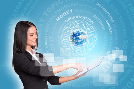 Beautiful businesswomen in suit using digital tablet. Earth with business words.  photo