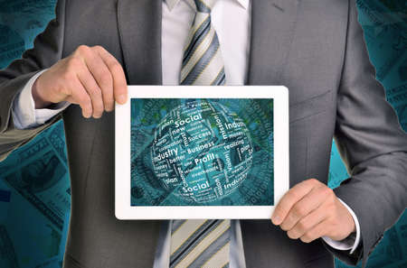 Man hands using tablet pc. Money and sphere of business words on touch screen. Money as backdrop photo