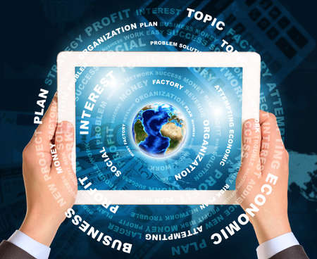 Man hands using tablet pc. Earth and business words on touch screen.   photo