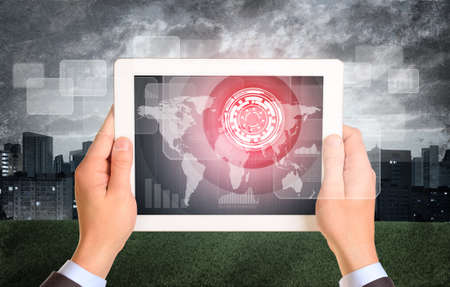 Man hands using tablet. Virtual elements on touchscreen. City as backdrop photo