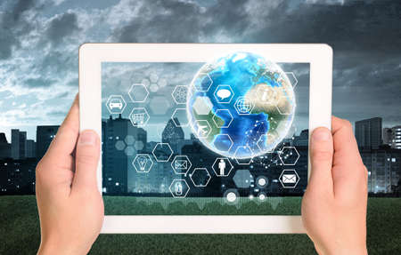 Man hands using tablet pc. Earth and hexagons with icons on touch screen. Element of this image furnished by NASA photo