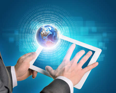 Man hands using tablet pc. Earth and figures near tablet.  photo