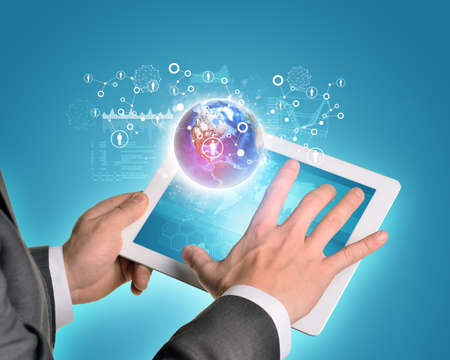 using tablet: Man hands using tablet pc. Earth and network people icons near tablet.