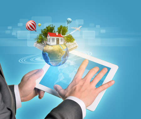 Man hands using tablet pc. Earth with buildings and trees near tablet.   photo