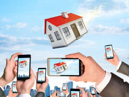 ?real estate?: Manos que sostienen los tel�fonos inteligentes y grabar v�deos como pertenecientes casa. Ciudad en el fondo Foto de archivo